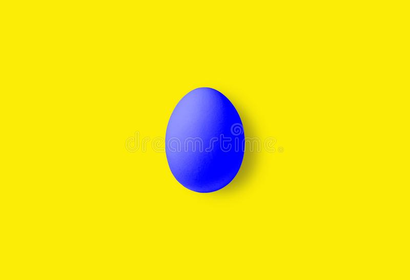 One blue egg on a yellow background. Close-up stock photo