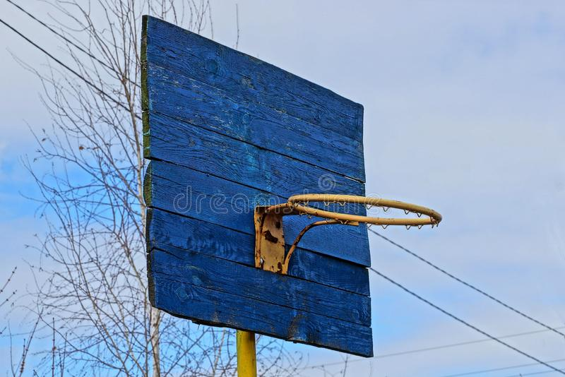 Blue old wooden basketball backboard with a yellow ring against the sky and branches stock photography