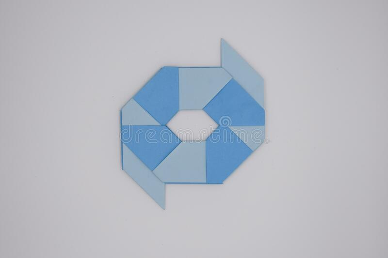 8 pointed ninja star paper fold. One blue paper fold of 8 pointed ninja star was taken royalty free stock photography