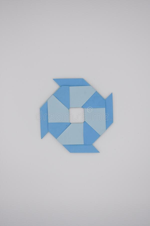 8 pointed ninja star paper fold. One blue paper fold of 8 pointed ninja star was taken stock image