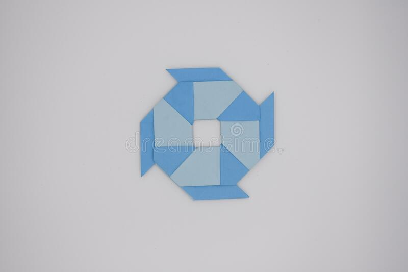 8 pointed ninja star paper fold. One blue paper fold of 8 pointed ninja star was taken royalty free stock image
