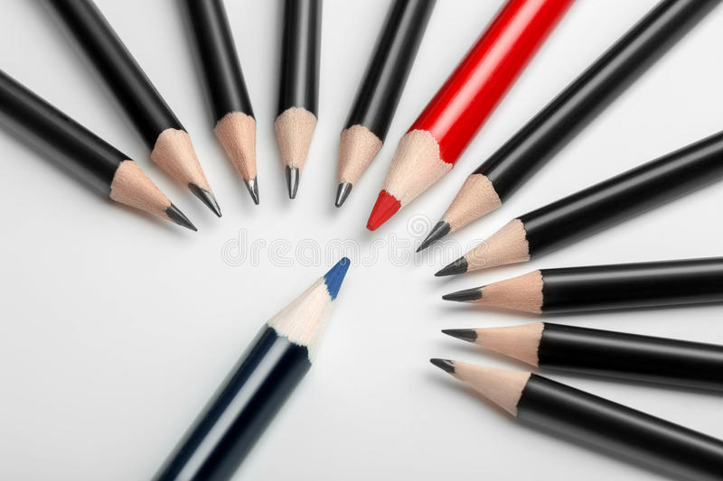One blue pencil against all black with red leader. Abstract gay discrimination. One blue pencil against all black with red leader. Abstract gay discrimination royalty free stock photo