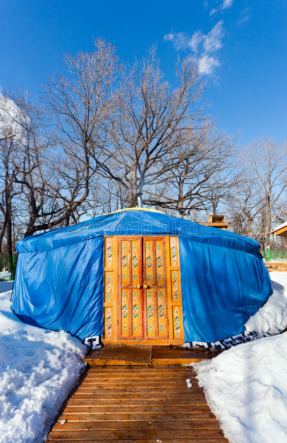 One blue yurt in the winter park. One blue yurt with big closed decorated orange door in the winter park stock image