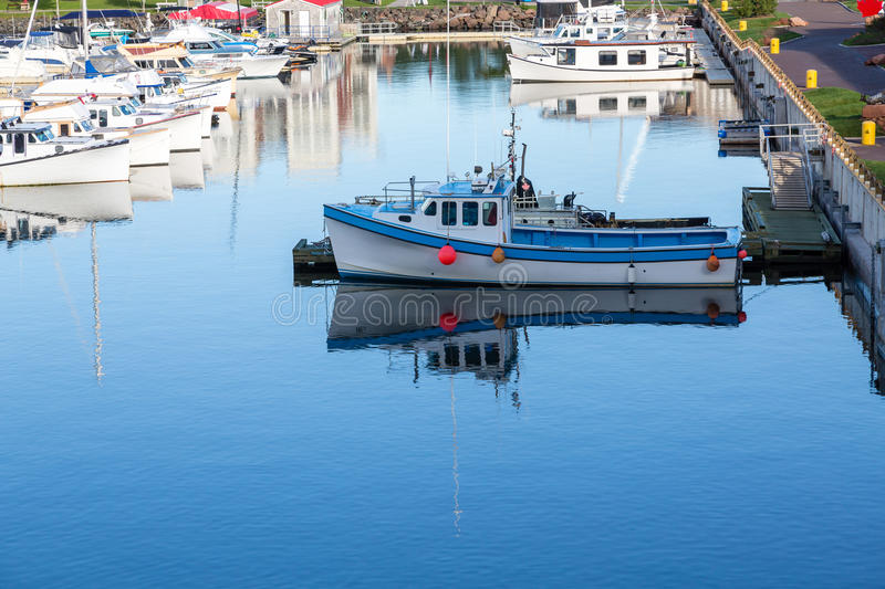 One Boat Alone. Small fishing boats in a calm blue harbor on Prince Edward Island in Canada royalty free stock photos