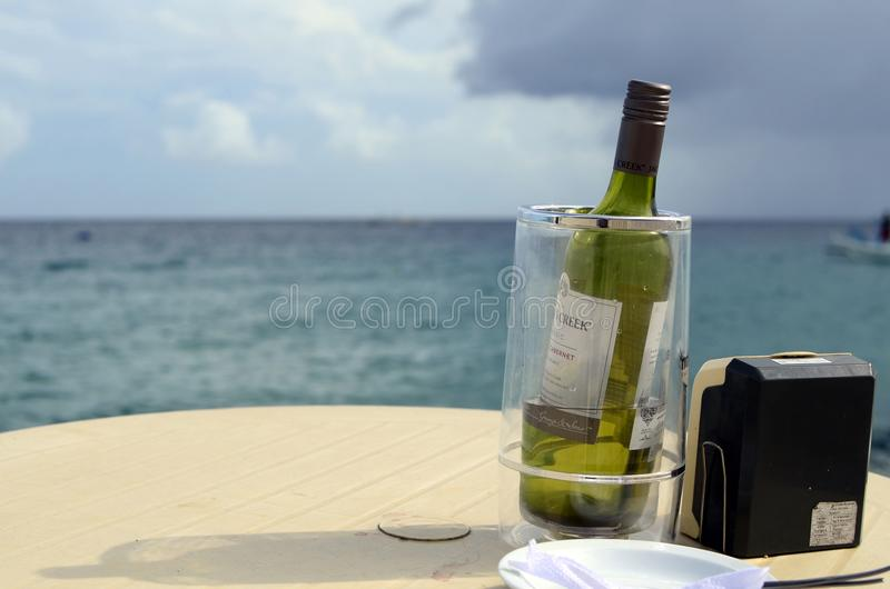 One bottle of vintage wine served to tourist in ice bucket at seaside resort royalty free stock photo