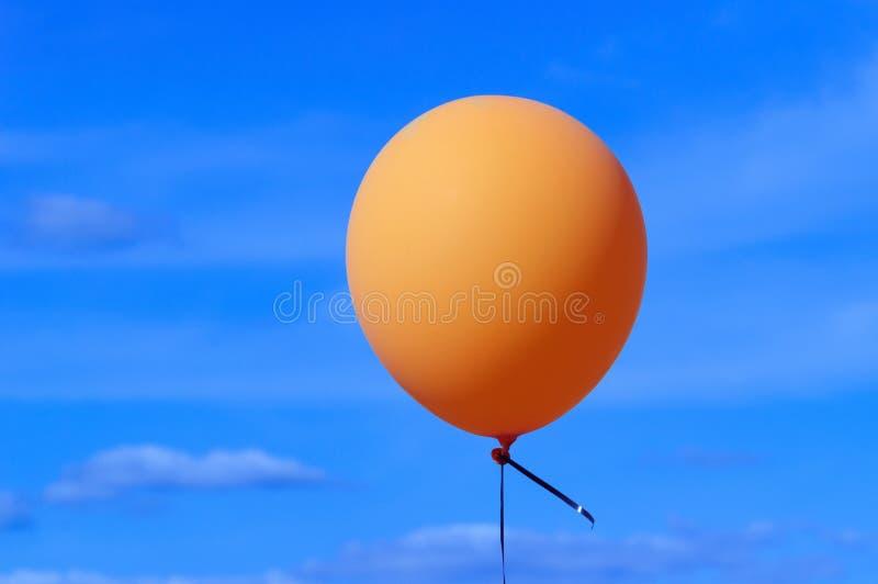 One bright orange balloon on blue sky. stock image