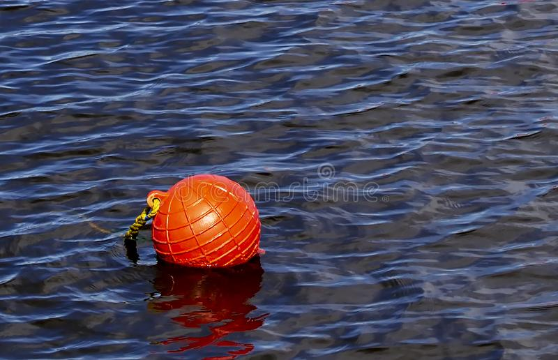 One bright orange buoy floating on lake water stock photography
