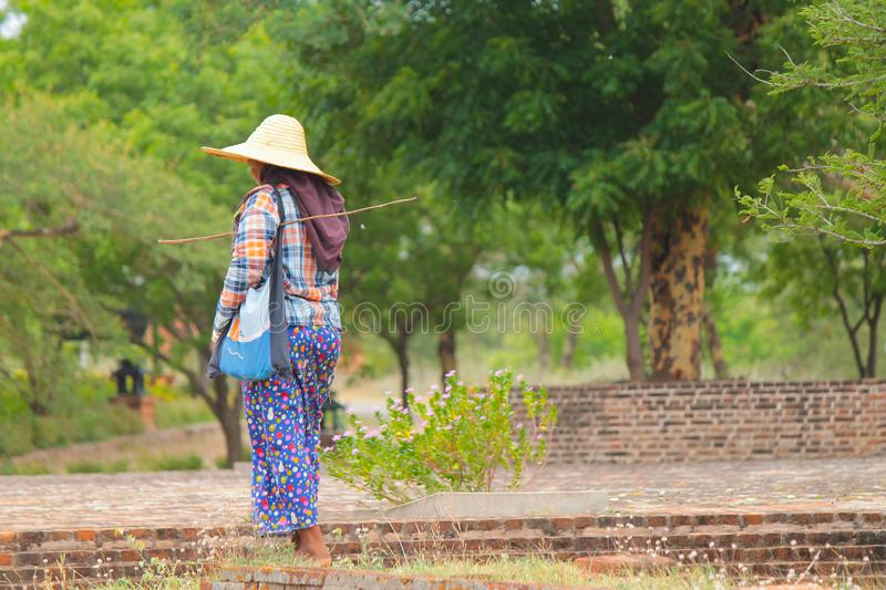 Burmese woman walking alone in Bagan with colorful outfits and straw hat. Bagan, Myanmar Burma. stock photos