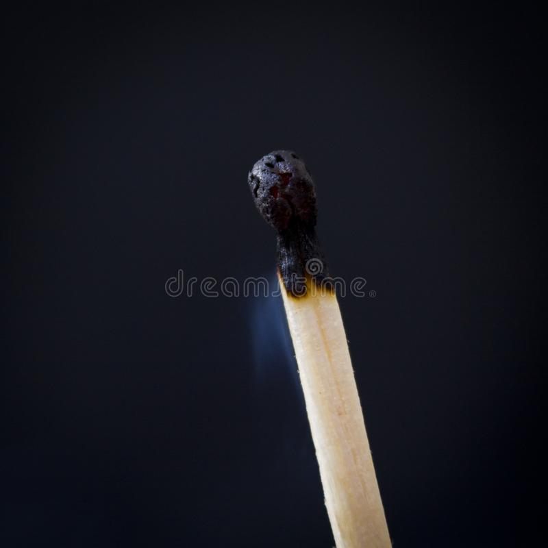 one burned match on a black background isolate stock photo