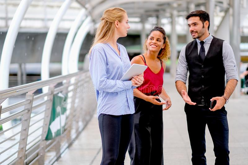One business man discuss about work with his team, two women with one mixed race tan skin and white Caucasian woman who holds stock image