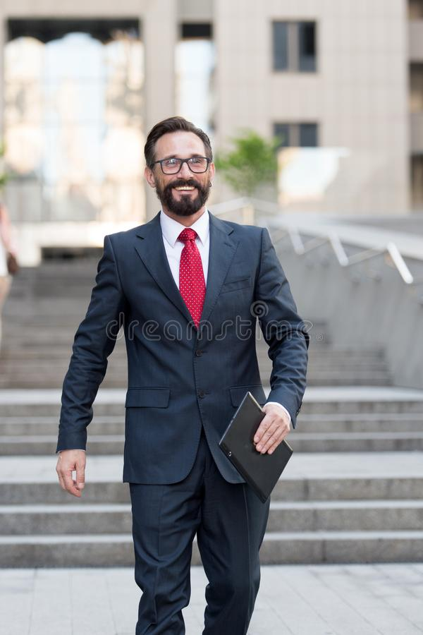 One Businessman stands at office building with tablet in hand. person dressed in business suit doing business affairs stock image