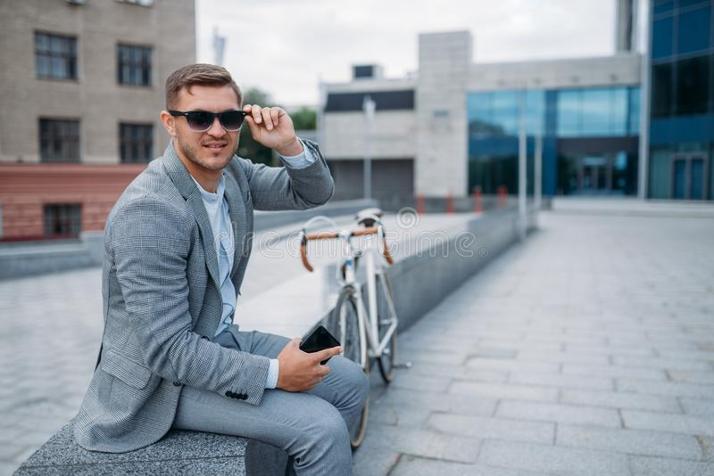 One businessman in sunglasses on bicycle, downtown stock photos