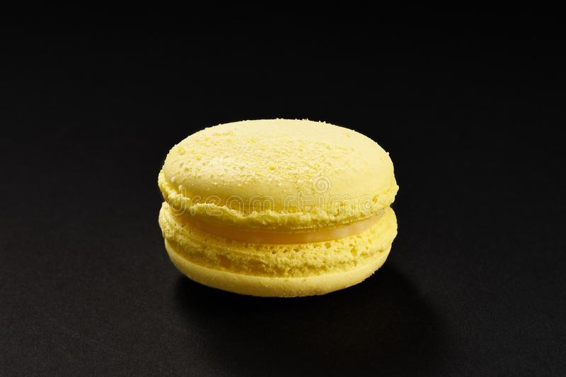 One cake of macaroni yellow lemon color. Delicious macaroon isolated on black background. French sweet cookie royalty free stock images