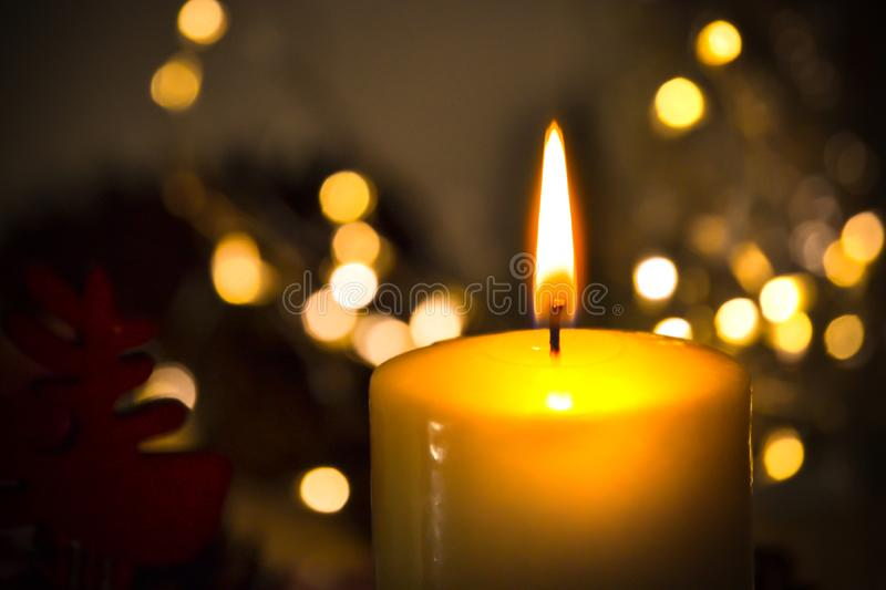 One candle burning brightly in the dark against a background of blurry lights. Romance, festive evening stock photos