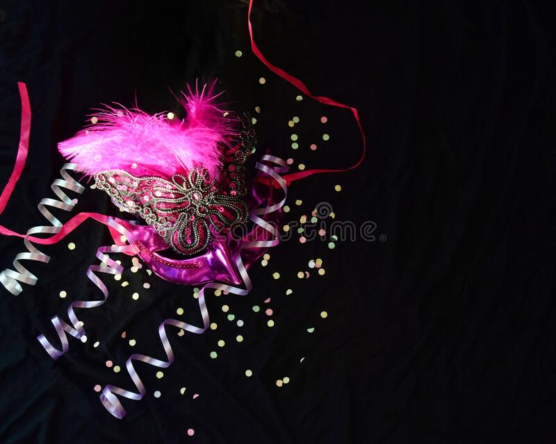 One carnival Venetian pink mask with feathers, mush and candy on a black background. selective focus. The Brazilian carnival is a celebration of masks and royalty free stock photo