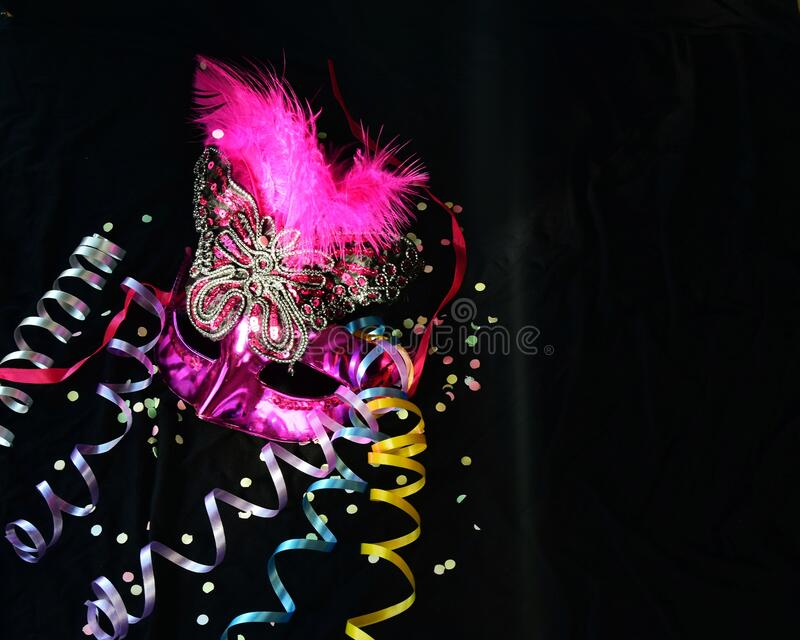 One carnival Venetian pink mask with feathers, mush and candy on a black background. selective focus. The Brazilian carnival is a celebration of masks and stock photos