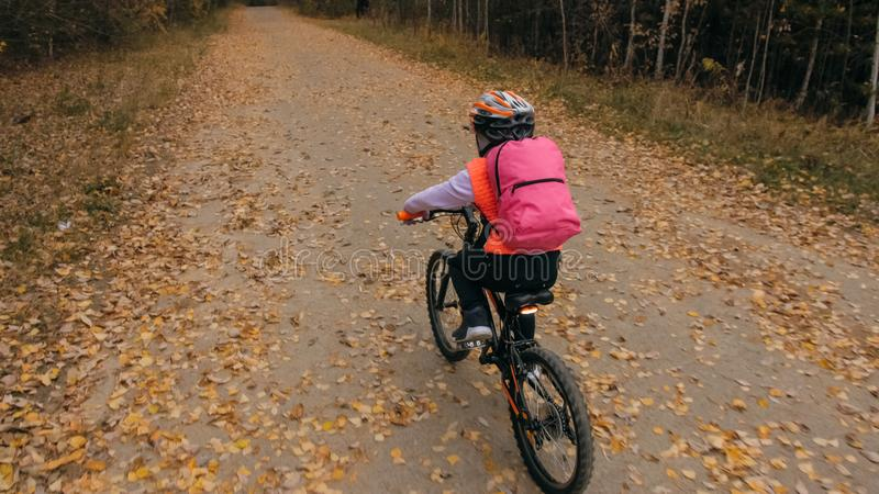 One caucasian children rides bike road in autumn park. Little girl riding black orange cycle in forest. Kid goes do royalty free stock photo