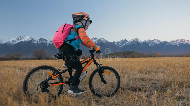 One caucasian children rides bike in wheat field. Little girl riding black orange cycle on background of beautiful snowy stock photo
