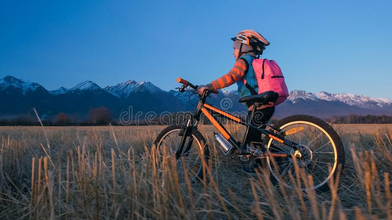 One caucasian children walk with bike in wheat field. Little girl walking black orange cycle on background of beautiful royalty free stock image
