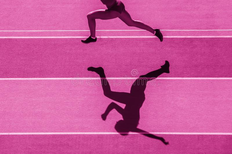 One caucasian woman runner jogger running in silhouette  on stadium background. Pink color filter royalty free stock photography