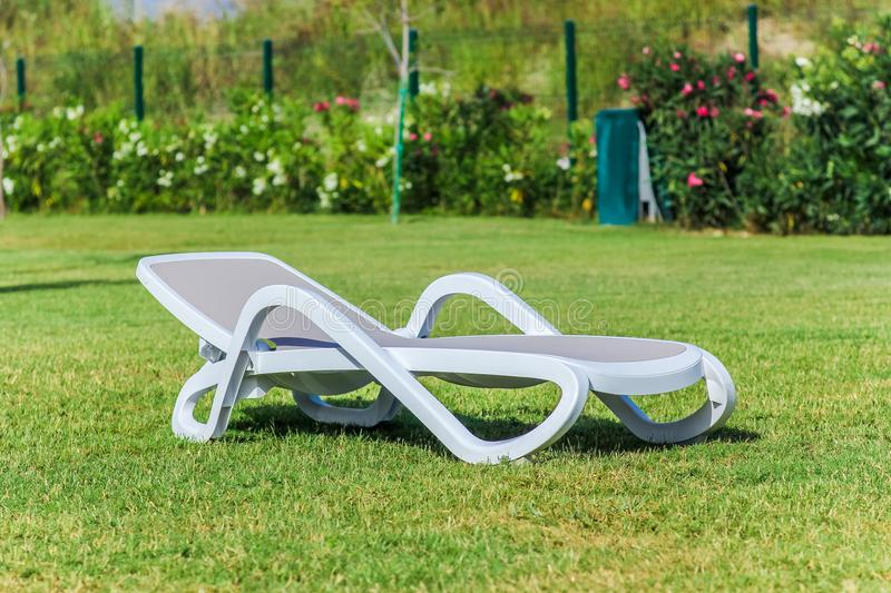 One chaise longue on the grass, close-up royalty free stock photos
