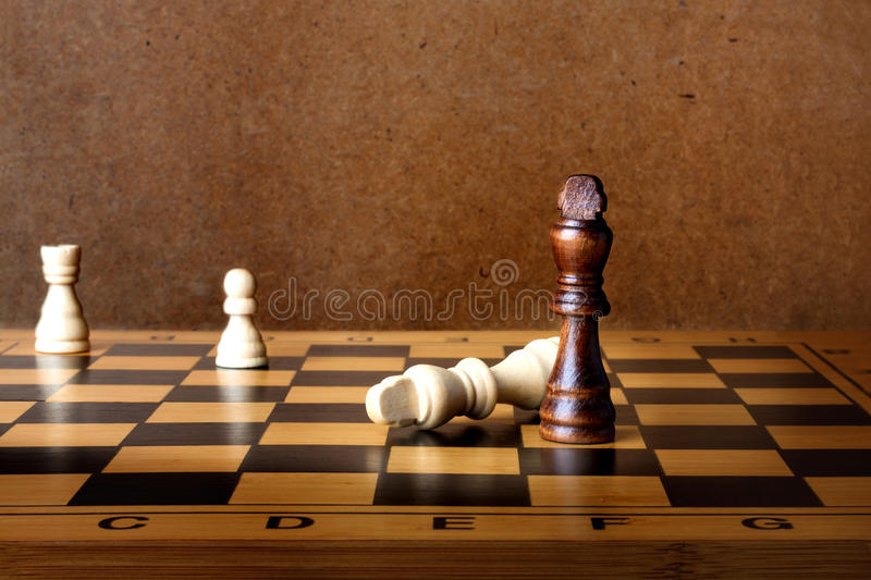One chess king dominating another. On the chessboard royalty free stock image