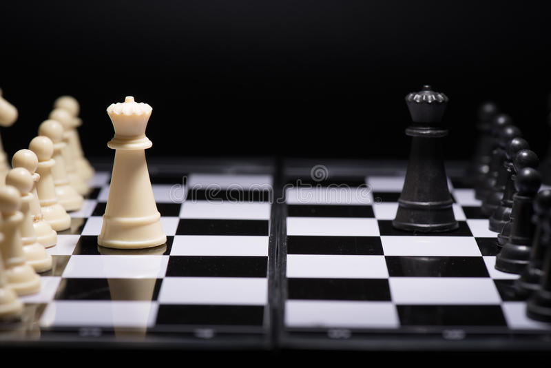 One chess pieces staying against black chess pieces stock photo