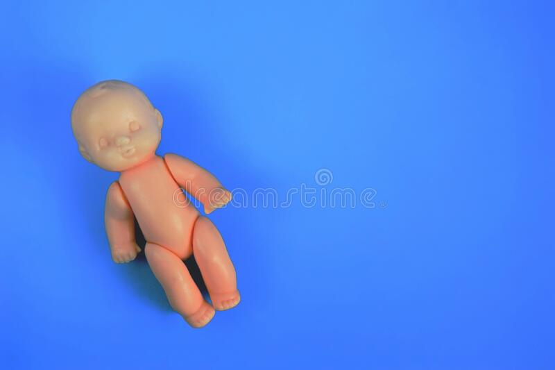 One childrens toy doll for children from one year on a blue background with a place for the inscription. close up.  stock photography
