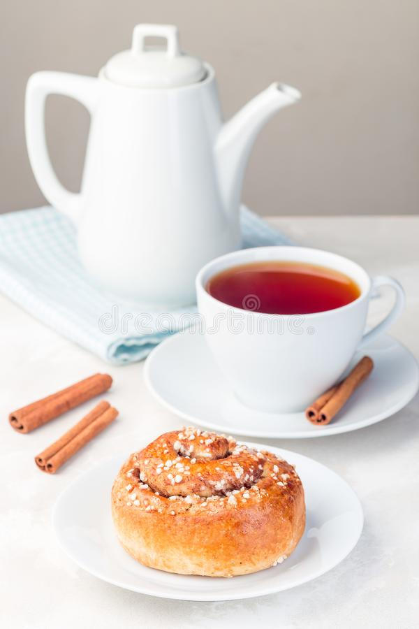 Free One Cinnamon Bun On A White Plate, Served With  Cup Of Red Tea, Vertical Royalty Free Stock Photos - 161057098