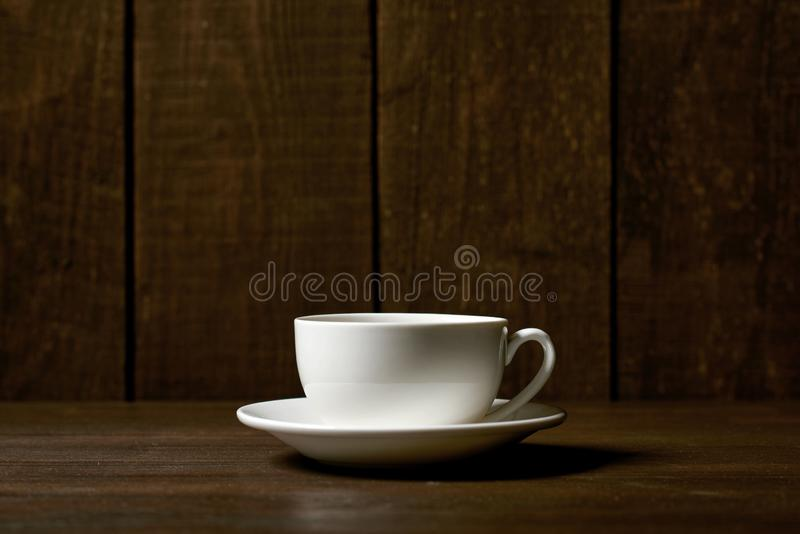 One classic coffee or tea cup on a dark wooden background royalty free stock images