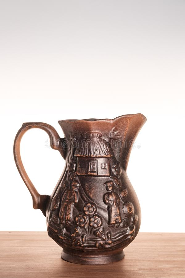One clay jug on a light gradient background. Jug handmade Ukrainian national motif. Subject shooting in the Studio. Vertical photography stock images