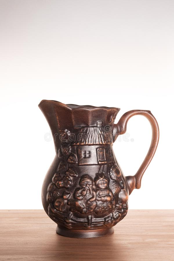 One clay jug on a light gradient background. Jug brown, handmade, Ukrainian national motif. Subject shooting in the Studio. Vertical photography stock image