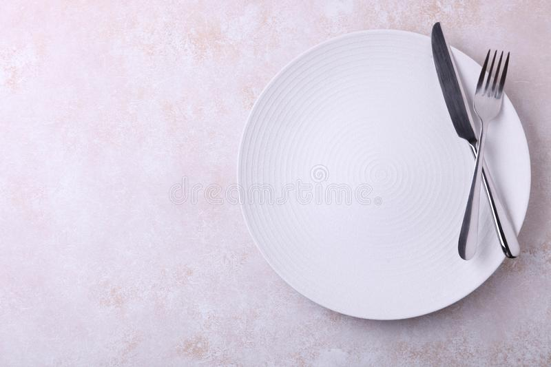 Empty plate and cutlery. One clean round empty plate and cutlery on neutral background. Concept dishes. Top view stock images