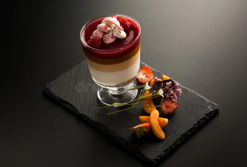 One cocktail in a glass with pieces of fruit on the decorative stone on a dark background. One cocktail in a glass with a raspberry and fruit pieces on the stock images