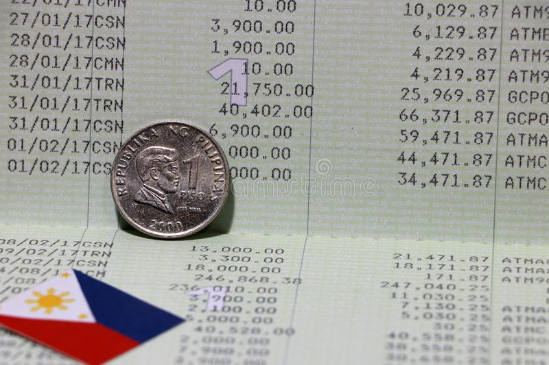 One coin of Philippine peso money on obverse and mini Philippine flag on the book bank. Concept of Saving money. Or finance royalty free stock image