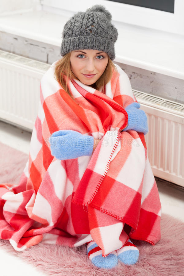 One cold evening. Freezing girl neat the heater stock photography