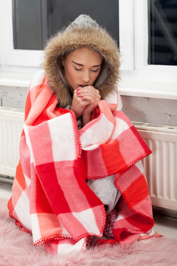 One cold evening. Freezing girl neat the heater stock images