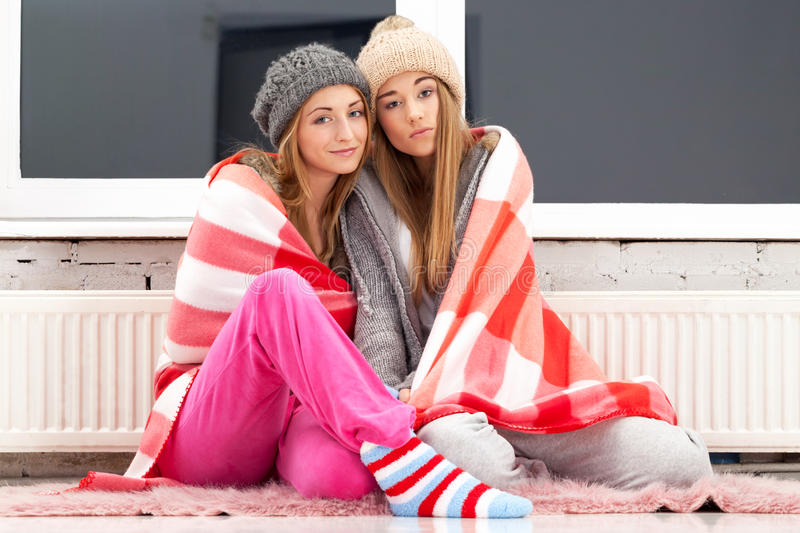 One cold evening. Two freezing girls near the heater royalty free stock photos