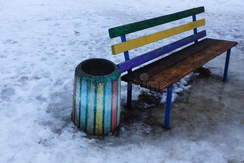 Colored wooden bench and concrete flowerbed outside in the snow stock photos