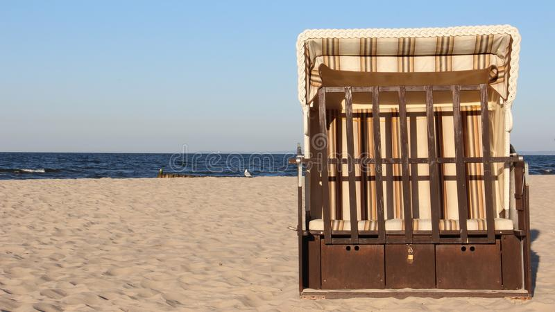 One Colorful Local Beach Chair On Baltic Seaside With Evening light. Free and Quiet. One Colored Local Traditional beach chair with warm sunshine and blue sky stock photography