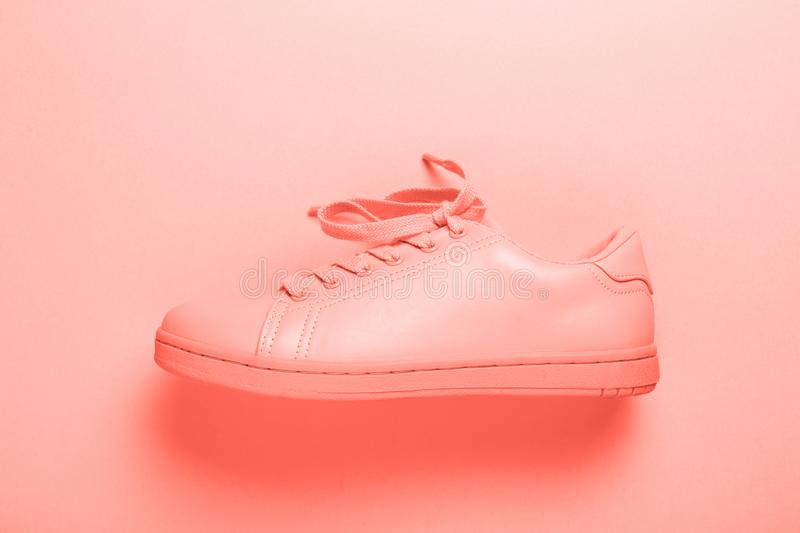One coral shoe on coral background. stock photo