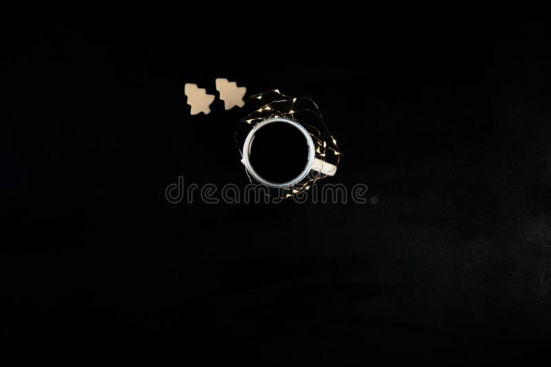 One cup with coffee on black table with christmas lights and cookies . Photograph taken from above, top view with copy royalty free stock photos