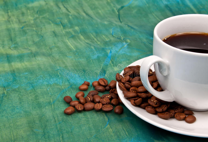 One cup of coffee with coffee beans around it royalty free stock photos