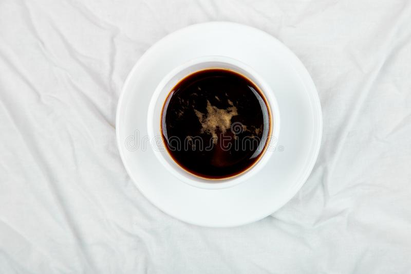 One Cup of coffee on white bed. Concept good morning. Lifestyle. Relax. Vacation. Copy space. Top view royalty free stock images