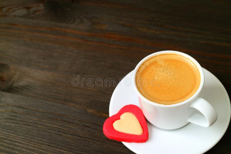 One cup of hot espresso coffee with a heart shaped cookie on dark brown wooden table with copy space stock image