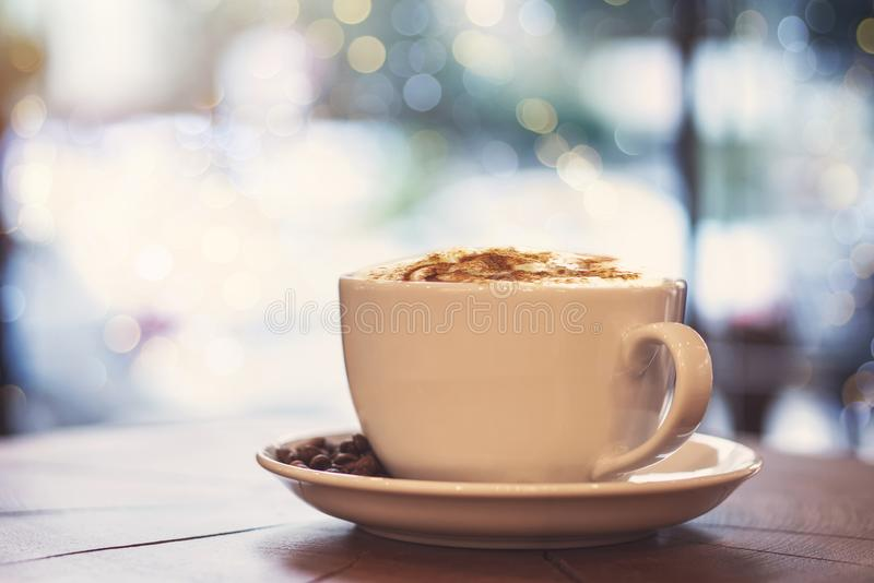 One cup of milk coffee and coffee beans on a wooden board royalty free stock photos