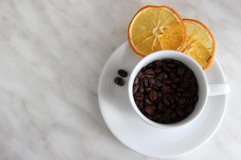 one Cup and saucer, coffee beans, slices of dried orange on a gray table top royalty free stock photo