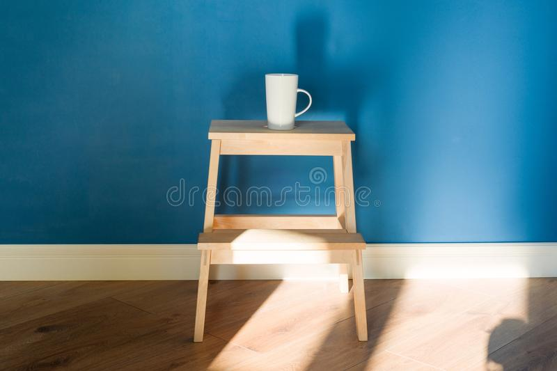 One cup stands on a wooden chair. Background blue matte wall with white plinth molding royalty free stock photos