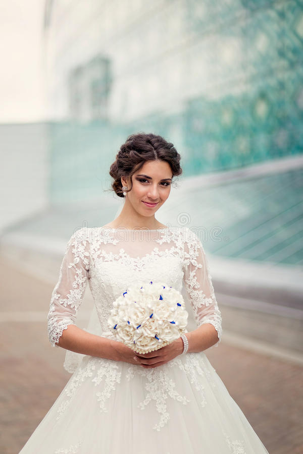 One Cute bride on the background of glass urban architecture stock image