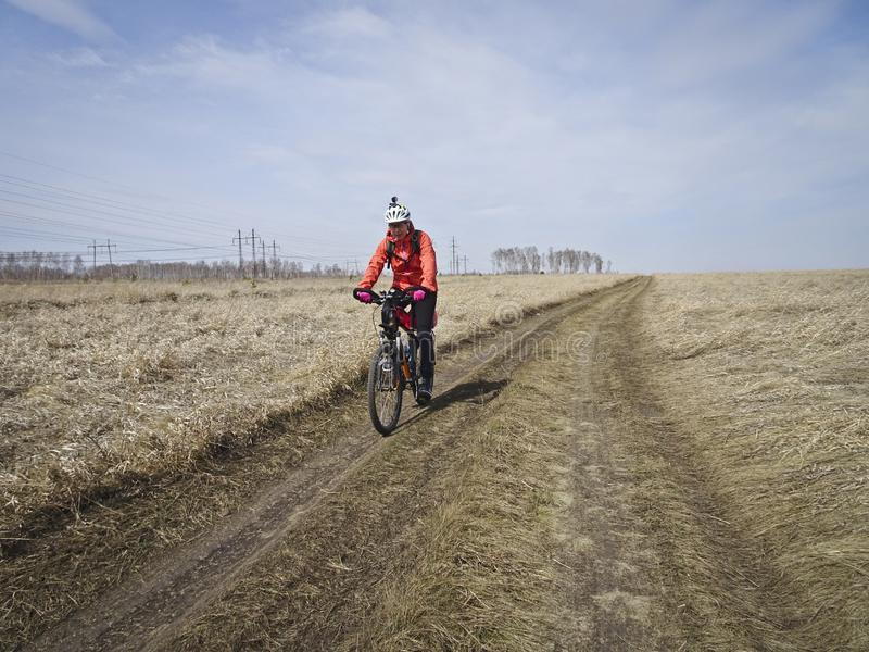 One cyclist in bright clothes rides on the field road among the endless steppes in spring. One cyclist in bright clothes rides on the field road among the royalty free stock images